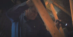 Inspector shines flashlight in dark attic